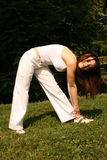 Stretching. A woman stretching outside in the grass Stock Images