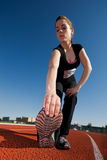 Stretching. A beautiful woman athlete stretching before a race (main focus on shoe Royalty Free Stock Photo