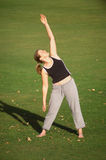 Stretching. Female exercising in the park, doing warm up stretches Stock Photos
