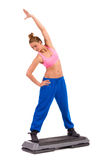 Stretching on aerobic step Royalty Free Stock Images
