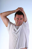 Stretching arm. Man in white t-shirt stretching arm stock image