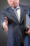 Stretching arm. Photo of senior businessman with arm stretched for handshake royalty free stock image