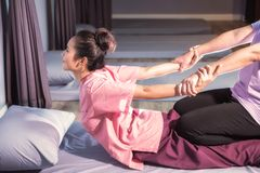 Stretching back and hands by Thai massage. Asian beautiful tan woman relax in spa. Body care treatment by Thai massage performed Hermit exercise. Cute girl with royalty free stock photo