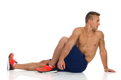 Stretching Back Muscle. Young fit man in blue shorts and orange sneakers sitting twisted on floor, looking back over the shoulder and stretching back, Side view Royalty Free Stock Images