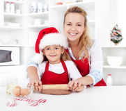 Stretching the christmas cookies dough. Women and little girl stretching the christmas gingerbread cookies dough Royalty Free Stock Images