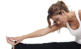 Stretching close up. A close up of a beautiful woman stretching before exercise, set against a white background Royalty Free Stock Photography