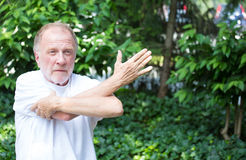 Stretching. Closeup portrait, senior mature man in white shirt, stretching arms, isolated green trees background. Warming up Stock Photo