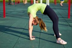 Stretching danser or gymnast woman training trains in workout sports ground. Doing exercise bridge royalty free stock image