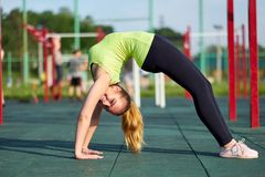 Stretching danser or gymnast woman training trains in workout sports ground. Doing exercise bridge royalty free stock photography