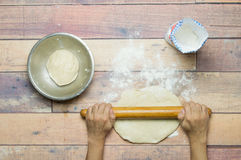 Stretching dough with rolling pin on wooden table. For cooking royalty free stock images
