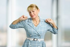 Stretching drowsy mature woman. Standing beautiful white-skin woman in dress, yawning and stretching close up stock photography