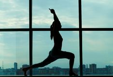 Stretching exercise. Silhouette of sporty girl doing physical exercise Royalty Free Stock Photography