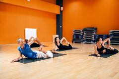 Stretching exercise, female yoga group in action. Training with instructor, workout in gym. Yogi indoor Stock Photo