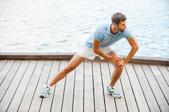 Stretching exercises. Confident young man doing stretching exercises while standing on quayside Royalty Free Stock Photo