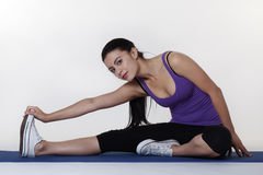Stretching exercises on a mat. Woman doing stretching exercises on a mat shot in the studio Royalty Free Stock Images