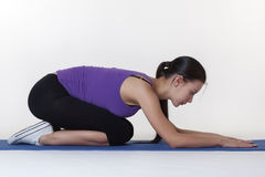 Stretching exercises on a mat. Woman doing stretching exercises on a mat shot in the studio Royalty Free Stock Image