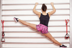 Stretching exercises. Pretty woman doing legs stretching exercises on bars Stock Image