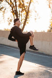 Stretching exercises before running training. On sunset urban background. Young male sportsman warming-up on open-air stadium. Healthy lifestyle, professional Stock Images