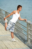 Stretching exercises before sport. Young athlete man doing stretching warming up before jogging outdoors Royalty Free Stock Photo