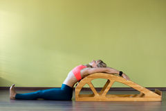 Stretching exercises on yoga backbend bench. Portrait of sporty beautiful young blond woman in sportswear working out indoors, doing exercise for spine Royalty Free Stock Photography