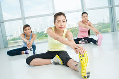 Stretching exercises. Young women doing stretching exercises in the aerobics class on the foreground Royalty Free Stock Photo