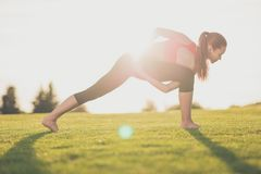 Stretching on fresh air. Wellbeing, wellness, vitality, peace li. Festyle. Young sporty woman is practicing yoga in the spring park outdoors in fashionable sport Royalty Free Stock Photos