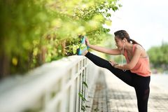Stretching girl. Asian female jogger stretching legs after training Royalty Free Stock Photography