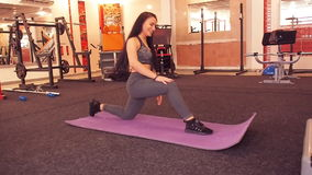 Stretching at the gym. Beautiful, athletic girl with her hair stretches the legs on the rug. stock footage