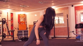 Stretching at the gym. Beautiful, athletic girl with her hair stretches the legs on the rug. stock video footage