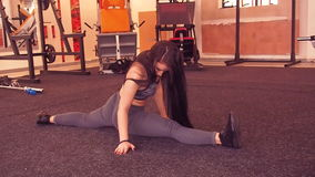Stretching at the gym. Beautiful, athletic girl with her hair stretches the legs on the rug. stock video