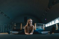 Stretching gymnast girl doing vertical split, twine. Side view of attractive young woman doing core exercise. At crossfit gym royalty free stock photos