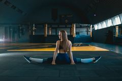 Stretching gymnast girl doing vertical split, twine. Side view of attractive young woman doing core exercise. At crossfit gym royalty free stock photo