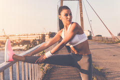 Stretching before jog. Beautiful young woman in sports clothing doing stretching exercises while standing on the bridge Royalty Free Stock Photo