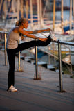 Stretching before jogging. Young woman doing stretching before jogging royalty free stock photography