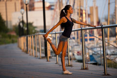 Stretching before jogging. Young woman doing stretching before jogging Stock Images