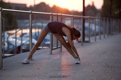 Stretching before jogging. Young woman doing stretching before jogging Royalty Free Stock Images