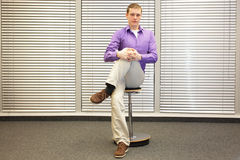 Stretching legs in office -  man sitting on pneumatic stool exercising Royalty Free Stock Image