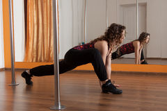 Stretching legs before pole dance. Young slim pole dance woman stretching Royalty Free Stock Image