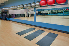 Stretching mats and exercise balls in gym. Stretching mats and silver and red exercise balls as seen in a club or gym Royalty Free Stock Photography