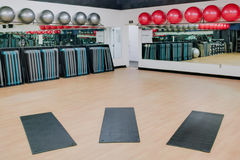 Stretching mats and exercise balls in gym. Stretching mats and silver and red exercise balls as seen in a club or gym Royalty Free Stock Images
