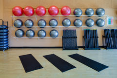 Stretching mats and exercise balls in gym. Stretching mats and silver and red exercise balls as seen in a club or gym Stock Images
