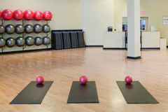Stretching mats and exercise balls in gym. Stretching mats and silver and red exercise balls as seen in a club or gym Royalty Free Stock Photo