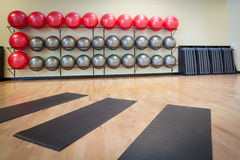 Stretching mats and exercise balls in gym. Stretching mats and silver and red exercise balls as seen in a club or gym Stock Photography