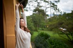 Stretching in the morning. Beautiful Asian woman stretching in the morning on balcony of resort hotel stock photos