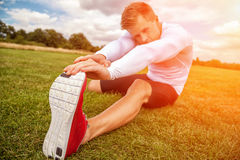 Stretching out in the park on a sunny day, with focus on hand Stock Photography
