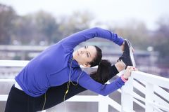 Stretching before running. Young woman doing some warm-up exercises before running Royalty Free Stock Images