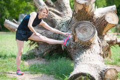 Stretching before running. Young woman stretches before running Royalty Free Stock Photos