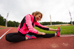 Stretching before running. Young woman stretches before running. Photo is taken with fisheye lens Royalty Free Stock Photo