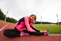 Stretching before running. Young woman stretches before running. Photo is taken with fisheye lens Stock Photos