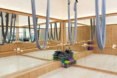 Stretching studio interior with aerial yoga silk hammocks and mirrors. Stretching studio interior with aerial yoga silk hammocks, brick walls and mirrors royalty free stock image